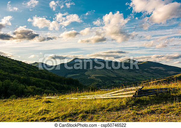 grassy hillside in mountains at sunset - csp50746522