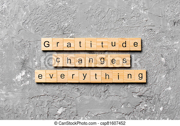 Gratitude changes everything word written on wood block. Gratitude changes everything text on cement table for your desing, concept - csp81607452