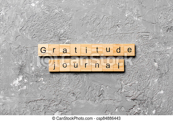 Gratitude Journal word written on wood block. Gratitude Journal text on cement table for your desing, concept - csp84886443