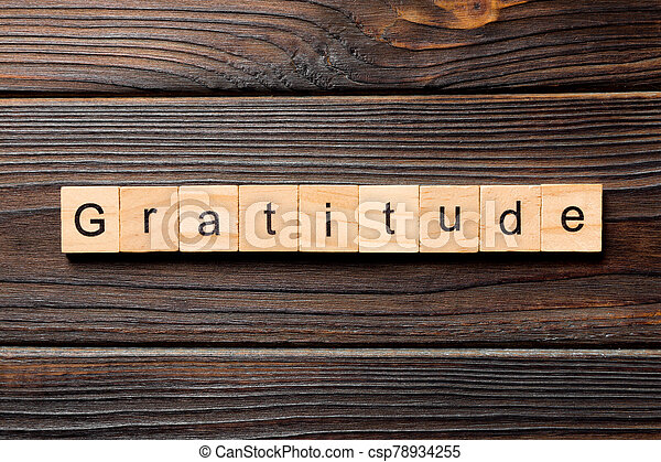 gratitude word written on wood block. gratitude text on wooden table for your desing, concept - csp78934255