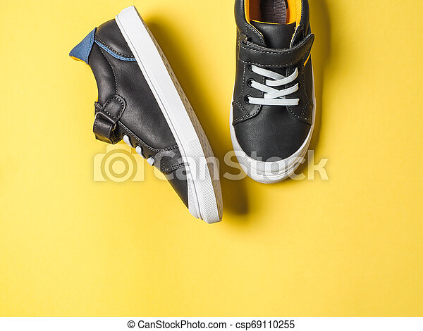 Gray and yellow sneakers on yellow background - csp69110255