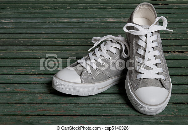 gray sneakers on a wooden background - csp51403261