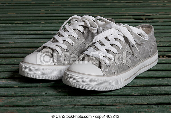 gray sneakers on a wooden background - csp51403242