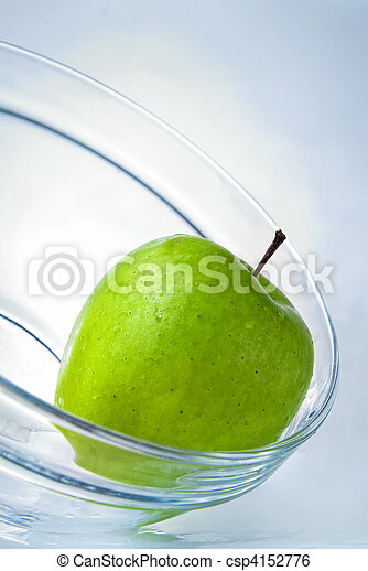 green apple in glass plate on blue background - csp4152776