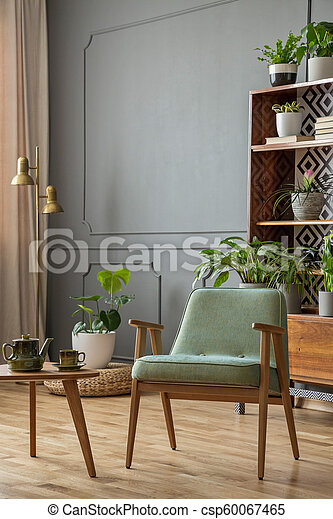 Green armchair next to wooden table in grey vintage living room interior with plants. Real photo - csp60067465