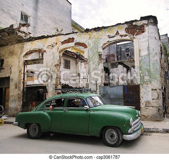 Green car on eroded havana street, cuba - csp3061787