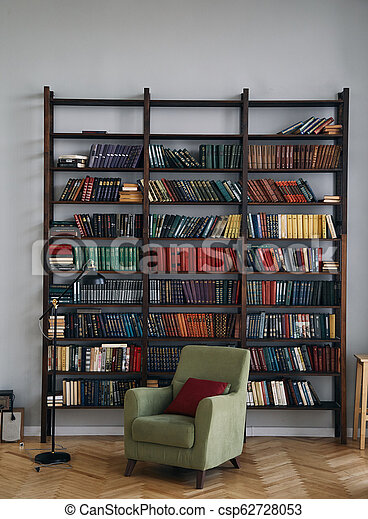 green chair in the interior. Bookcase with old books on the shelves. Books in an old wooden Cabinet - csp62728053