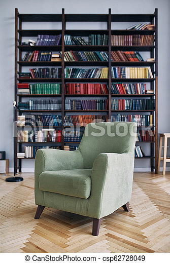 green chair in the interior. Bookcase with old books on the shelves. Books in an old wooden Cabinet - csp62728049