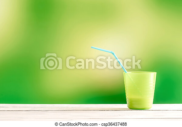 Green cup with a blue straw - csp36437488