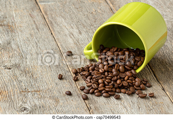 Green cup with scattered coffee beans - csp70499543