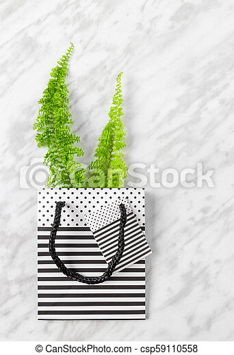 Green fern branches in a gift bag on marble background - csp59110558