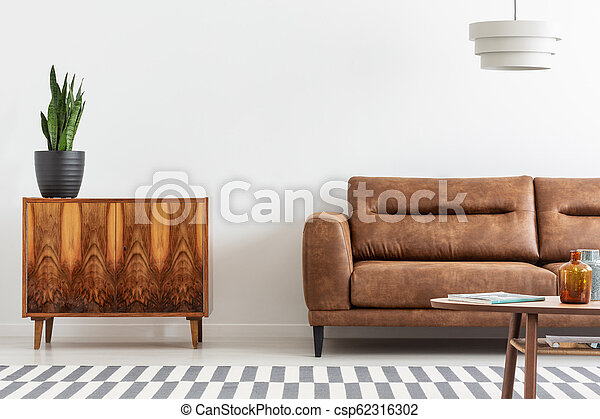 Excellent Green Flower In Black Pot On Vintage Cupboard Next To Big Comfortable Brown Leather Sofa Real Photo With Copy Space Pdpeps Interior Chair Design Pdpepsorg