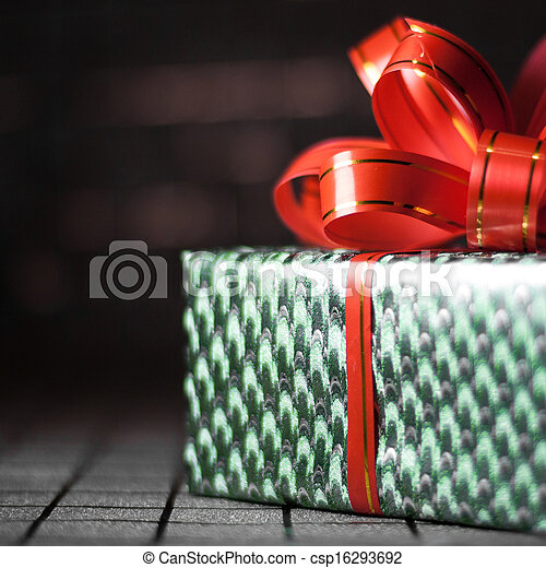 Green gift box with a red ribbon on background close-up - csp16293692