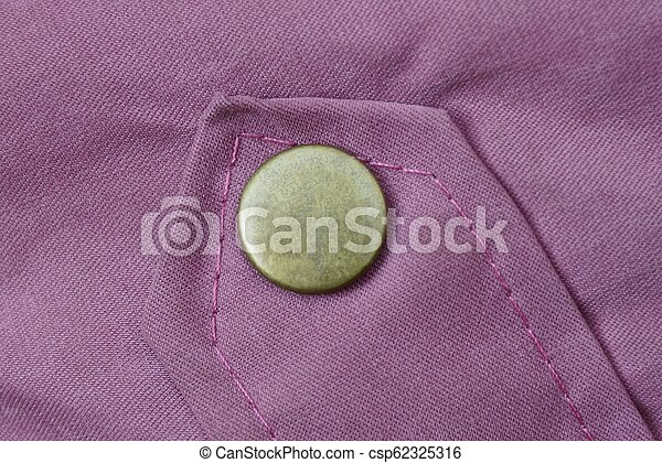 green iron button rivet on the red fabric sleeve on the clothes - csp62325316