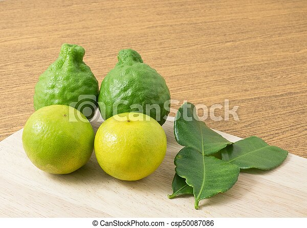 Green Kaffir Lime with Lemon Lime on Cutting Board - csp50087086