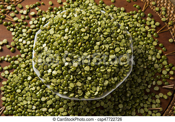 Green lentils inside a white pot on wood background  Edible raw pulses of  the legume family