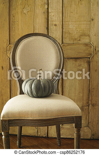 Green pumpkin on chair - csp86252176