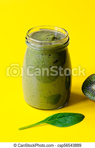 Green smoothie with kiwi and leaf of spinach on yellow background - csp56543889