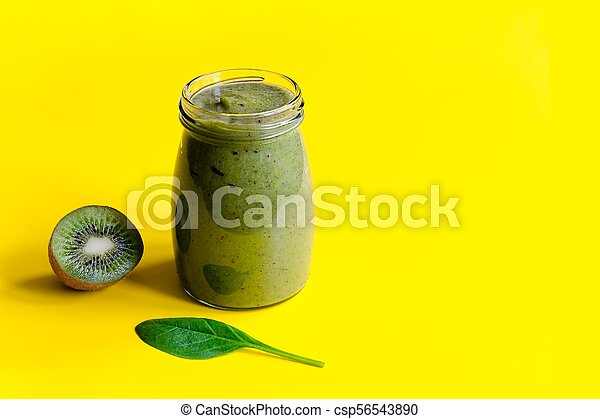 Green smoothie with kiwi and leaf of spinach on yellow background - csp56543890