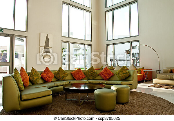 Green sofa in bright modern lobby. A green sofa with orange cushions ...