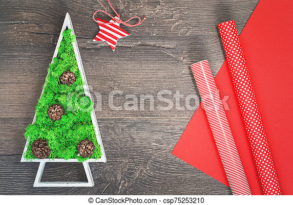 Green stabilized Christmas tree and red gift wrapping paper - csp75253210