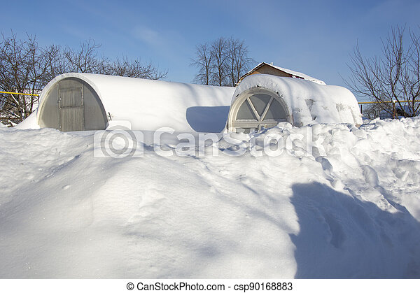 Greenhouses in the snow. There is a lot of snow in the garden. Winter day in the village. Winter in the garden. Greenhouses brought up to the very top. - csp90168883