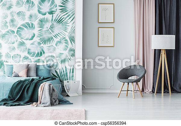 Grey armchair in green bedroom