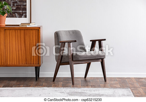Grey armchair next to wooden cabinet with plant in grey retro living room interior. Real photo - csp63215230