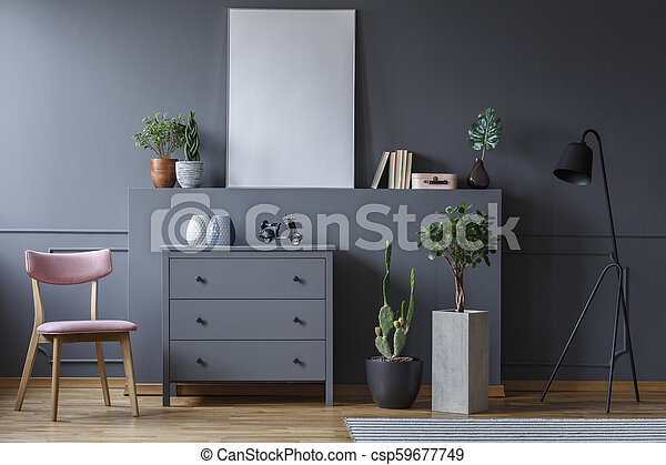 Grey cabinet between wooden chair and plants in living room interior with mockup of poster. Real photo - csp59677749