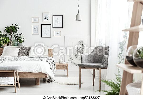 Grey chair in bright bedroom - csp53188327