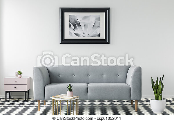 Grey couch between cabinet and plant in simple living room interior with poster and table. Real photo - csp61052011