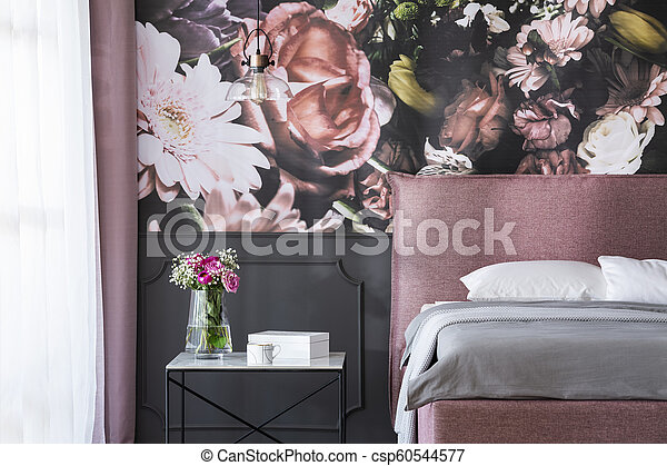 Grey cushions on pink bed next to table with flowers in bedroom interior  with wallpaper. Real photo