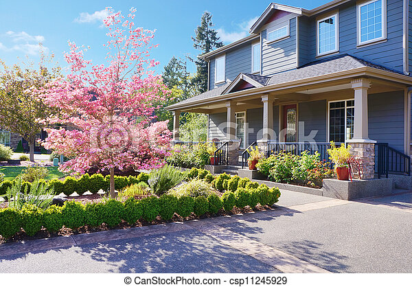 Grey large luxury house with spring blooming trees. - csp11245929