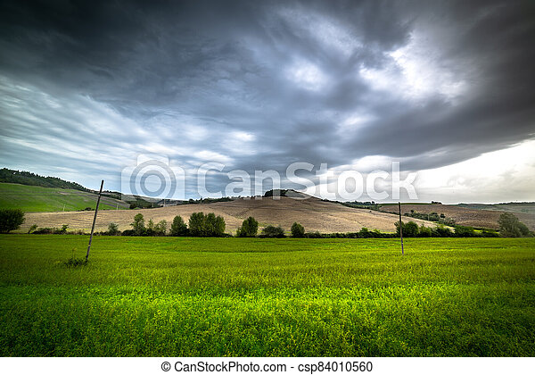 Grey sky over a small hill in Tuscany - csp84010560