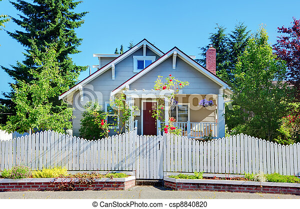 Grey small cute house with white fence and gates. - csp8840820