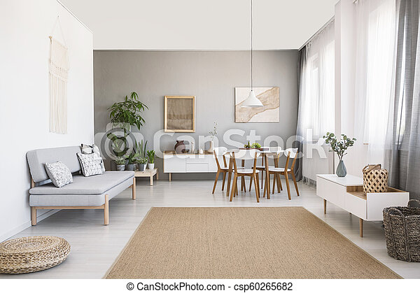 Grey sofa near white chairs at dining table in bright living room interior  with brown carpet. Real photo