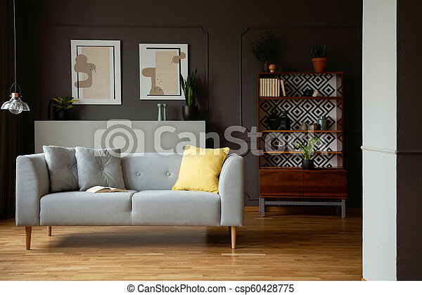 Grey Sofa With Yellow Cushion In Vintage Living Room Interior With Posters And Lamp Real Photo