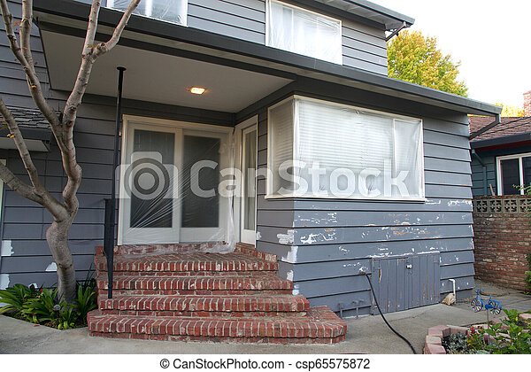 Grey two story house with stucco patching prior to patching - csp65575872
