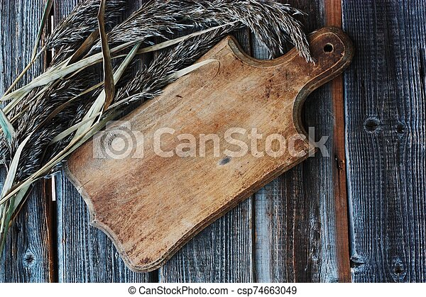 Grey wooden background and rye close up - csp74663049