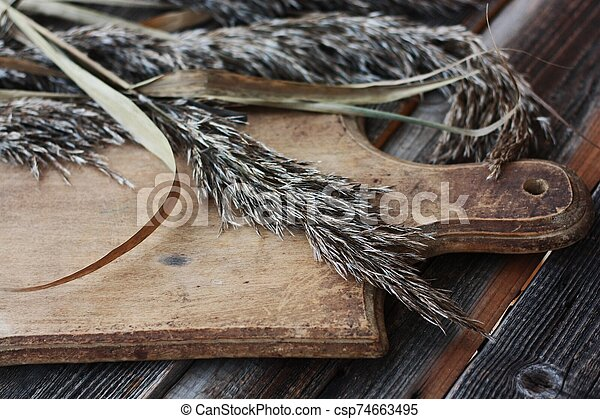Grey wooden background and rye close up - csp74663495