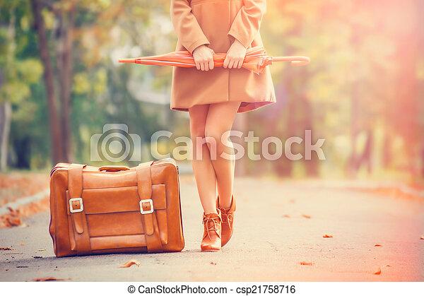 Asado en abrigo con paraguas y maleta en el parque. - csp21758716