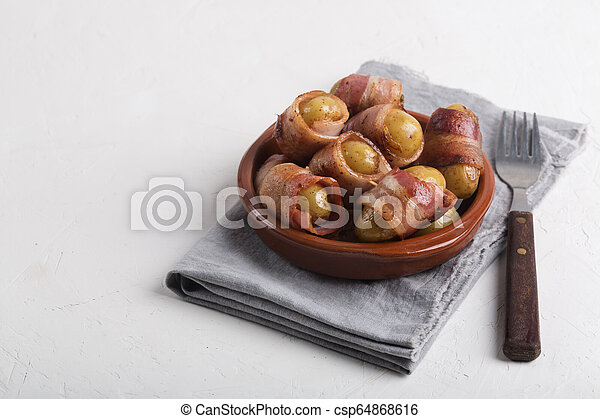 Grilled baby potato wrapped in bacon on the white background - csp64868616