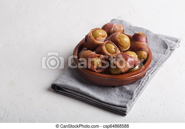 Grilled baby potato wrapped in bacon on the white background - csp64868588