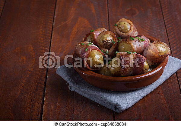 Grilled baby potato wrapped in bacon on the wooden background - csp64868684