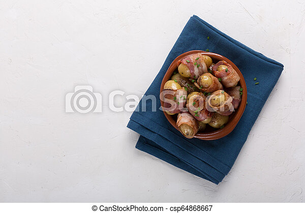 Grilled baby potato wrapped in bacon on the white background - csp64868667