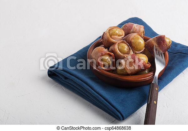 Grilled baby potato wrapped in bacon on the white background - csp64868638