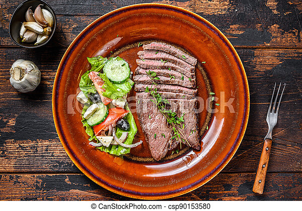 Grilled beef meat chop round steak on a plate with salad. Dark wooden background. Top view - csp90153580