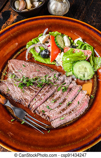 Grilled beef meat chop round steak on a plate with salad. Dark wooden background. Top view - csp91434247