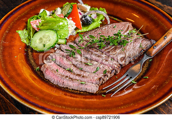 Grilled beef meat chop round steak on a plate with salad. Dark wooden background. Top view - csp89721906