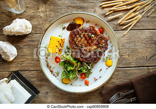 Grilled beef steak with corn on wooden background - csp90859908